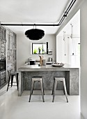 Designer bar stools at concrete counter in kitchen with rustic grey cupboards