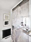 Blick durch transparenten Raumteiler in Wohnbereich mit weißem Bodentisch und Sitzsäcken