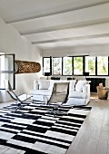 White couch and armchairs on black and white rug in lounge