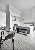 Vintage armchair in front of grey double bed and partition wall with interior window
