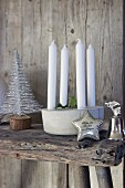 Candle arrangement, stylised Christmas tree, silver star and silver bell on wooden bench