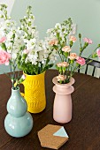 Verschiedenfarbige Vasen mit Blumen und Korkuntersetzer