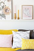 Pink and yellow patterned scatter cushions on sofa below pictures on narrow shelf