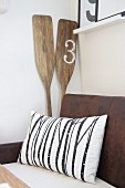 Cushion on vintage bench and wooden oars in corner