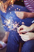 Lit sparklers in hands