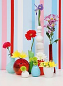 Collection of colourful vases holding various flowers in front of walls painted with vertical stripes