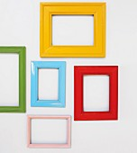 Picture frames painted various colours hung on white wall