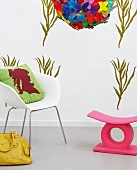 DIY wall design with green stencilled pattern, white armchair with cushion, yellow leather bag and pink stool