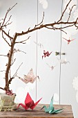 Various origami cranes hung from branch as mobile and on table