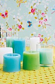 DIY pastel candles poured into drinking glasses against floral wallpaper