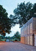Building with modern perforated façade elements, paved courtyard and view into park-style gardens at twilight