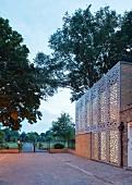 Gebäude mit modernen, gelochten Fassadenelementen, gepflasterter Vorplatz und Blick in Parkanlage bei Dämmerstimmung