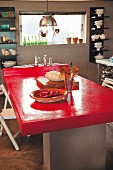 Bright red tabletop in kitchen with crockery on wall-mounted shelves