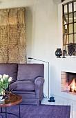 Loungeecke mit Kaminfeuer, Kaminspiegel und Holzskulptur
