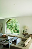 Rustic coffee table in comfortable lounge and view of garden through arched window