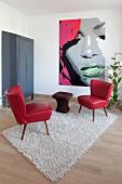 Schlicht eingerichtetes Wohnzimmer mit Retromöbeln und Pop Art Bild