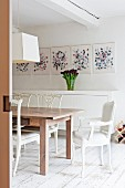 Wooden table, white chairs, white sideboard and modern art in dining area with vintage wooden floor