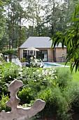 Kleines Haus mit Pool im sommerlichen Garten mit Bäumen