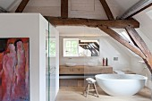 Bathroom behind glass wall in converted attic with rustic roof beams