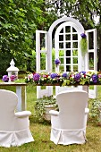 Outdoor wedding with lattice frame and flower arrangements