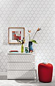 A red upholstered stool next to a wallpapered chest of drawers in front front of wallpaper with the same grey tile pattern