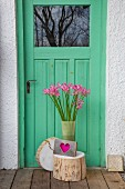 Vase of pink nerines on slice of tree trunk against front door