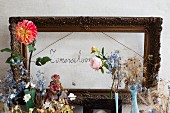 Vintage-style flower arrangement in front of antique picture frame around hand-written motto on wall