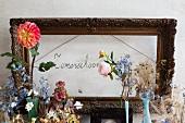 Blumenarrangement mit Vintage Flair vor antikem Bilderrahmen und Handschrift an Wand