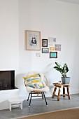 Sessel mit Schaffell und Hocker mit Pflanze vor Bilderwand