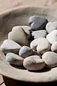 Holzschale mit herzförmigen Steinen