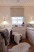 Sprossenfenster und Kommode zwischen zwei Betten