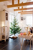 Tablett-Tisch mit Schnitzerei, brennenden Kerzen und Süßigkeiten vor Weihnachtsbaum