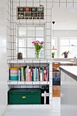 White wall tiles, interior window and open-fronted fitted shelves in kitchen