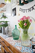Glass vase of tulips on colourful cement-tiled top of retro sideboard