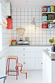 Retro scales and colourful tins in white fitted kitchen on String shelves