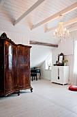 Antiker, kunsthandwerklicher Holzschrank in weißem Dachzimmer mit Kronleuchter und nostalgischem Flair