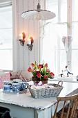 Adventsgesteck mit roten Tulpen auf Vintage Esstisch neben Brotkorb und Tablett mit Tassen