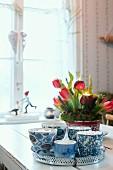Adventsgesteck mit roten Tulpen und Tannenzweigen in Blechdose, davor Tablett mit Tassen