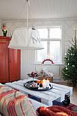 Tablett mit Weihnachtsdekoration auf Palettentisch im Wohnzimmer