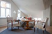 Tisch mit Balusterfuß und alte Stühle mit Husse unter der Schräge