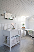 Washstand in white, wood-clad bathroom under sloping ceiling