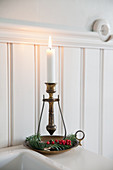 Antique candlestick decorated with fir sprigs and berries