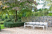 White outdoor furniture on gravel terrace with gabion wall in garden