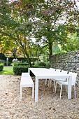 Kiesplatz mit weißen Outdoormöbeln vor Gabionzaun im Garten