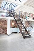 Stahltreppen zu zwei Galerieebenen in Loft mit Betonboden und rustikaler Ziegelwand