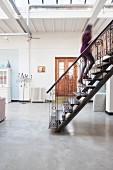 Stahltreppe mit kunsthandwerklichem Geländer in Loftwohnung mit Betonboden