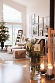 Glass vase of hellebores, candle lanterns on wooden floor and decorated Christmas tree in lounge area in background