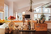 Vintage kitchen utensils in front of counter and decorated Christmas tree in living room in background
