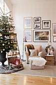Decorated Christmas tree in living room next to beige armchair, footstool and framed pictures on wall