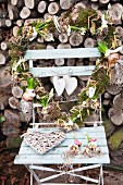 Heart-shaped wreath decorated with flowering bulbs on garden chair in front of stacked firewood